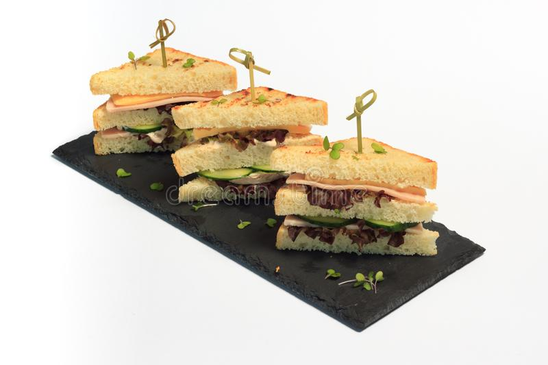 Triangle club sandwich tripple set on black ceramic plate against white background. Triangle club sandwich tripple set on black ceramic plate part of series royalty free stock photo