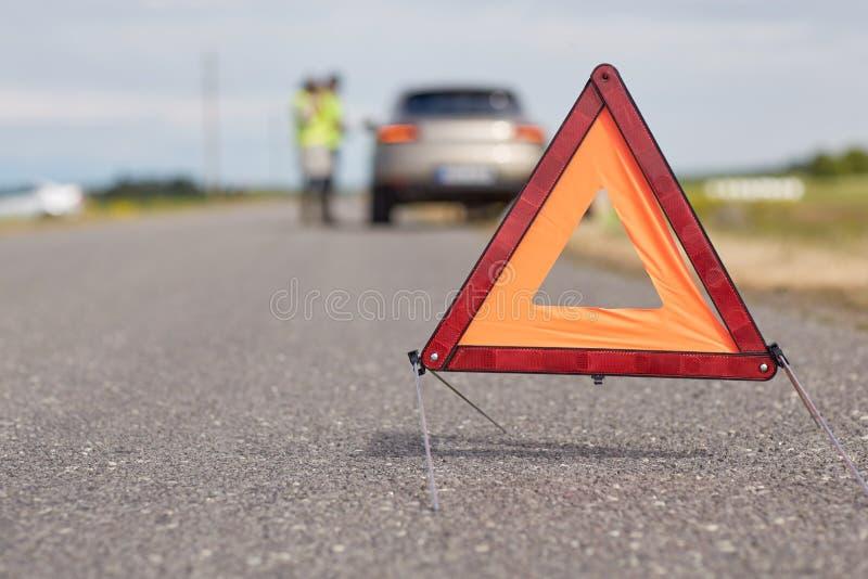 Triangle d'avertissement au-dessus de voiture cassée sur la route images libres de droits