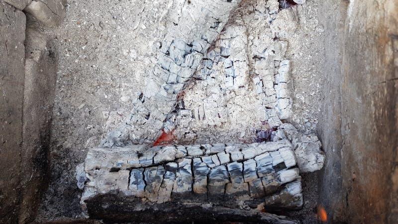 Triangle de bois de chauffage brûlée aux cendres Texture en bois brûlante fendue avec le fond gris de cendre Petites flammes roug image stock