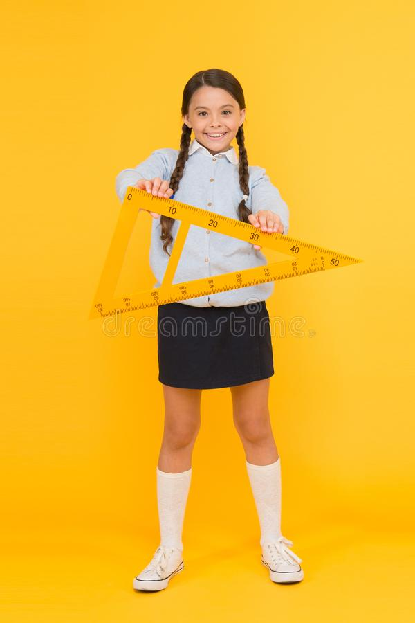 A triangle has three sides and three angles. Adorable happy schoolchild holding triangle on yellow background. Cute girl stock images