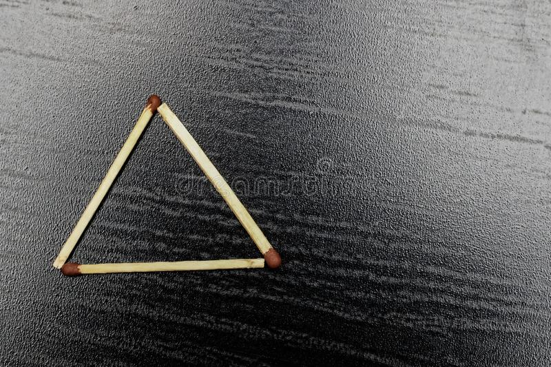 The triangle is made of matches on a black background. Copy space royalty free stock images
