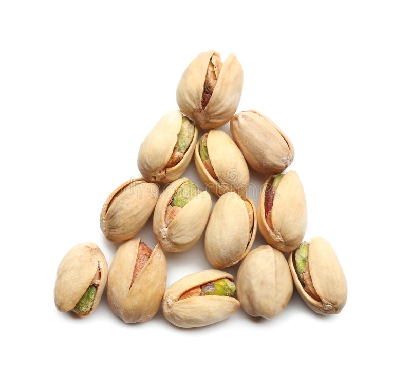 Triangle made of pistachio nuts on white background royalty free stock photo