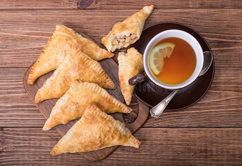 Triangle meat pies with cup of tea . Triangle meat pies with cup of tea on the wooden table royalty free stock image