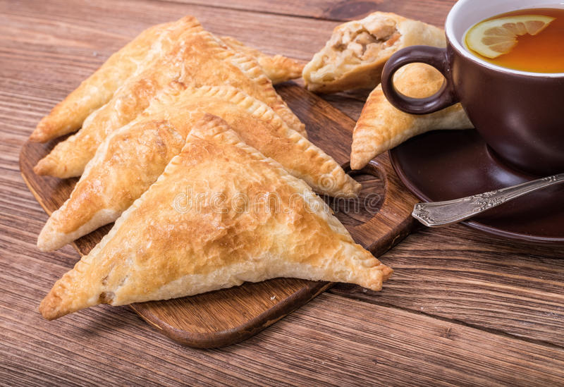 Triangle meat pies with cup of tea . Triangle meat pies with cup of tea on the wooden table royalty free stock photos