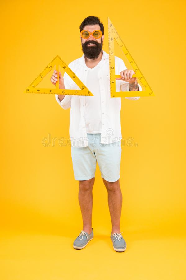 Triangle is the most important shape in engineering. Engineer using triangles for making engineering drawings. Bearded royalty free stock photo