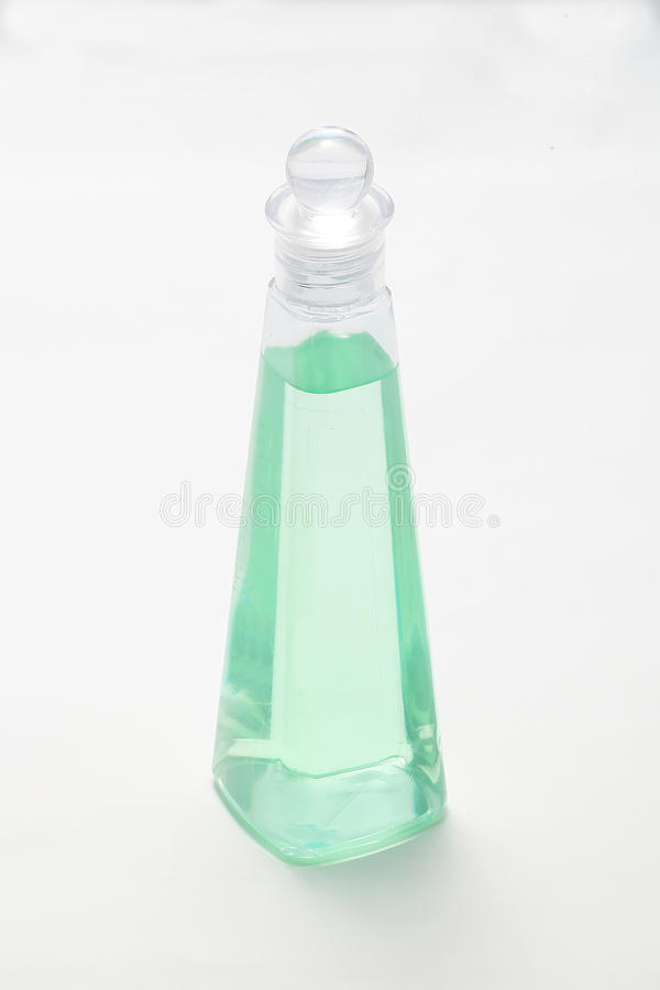 Triangle Shape plastic bottle. With green liquid on white background stock images