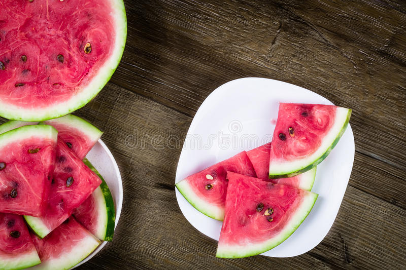 Triangle shaped watermelon slices placed in plate on dark grungy background. Top view. stock image