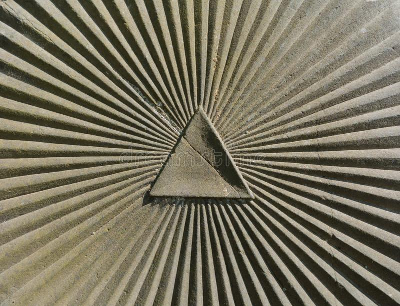 Triangle and sumbeam as a symbol for the eye of providence. Carved in an old marble stone stock photos