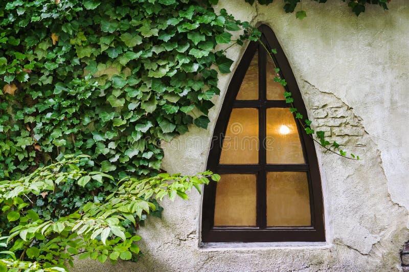 Triangle window on an old grunge wall stock photo