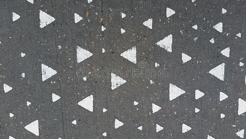 Triangles blanches peintes sur le béton image libre de droits