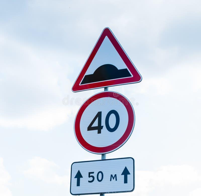 Triangulär konstgjord unevenness för trafikvägmärke efter 50 M för tvungen hastighetsförminskning med hastighetsbegränsningtecken royaltyfri foto