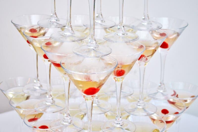 Triangulära martini exponeringsglas, med körsbär och vätskegasformigt grundämne som skapar ånga som byggs i formen av en pyramid arkivfoto