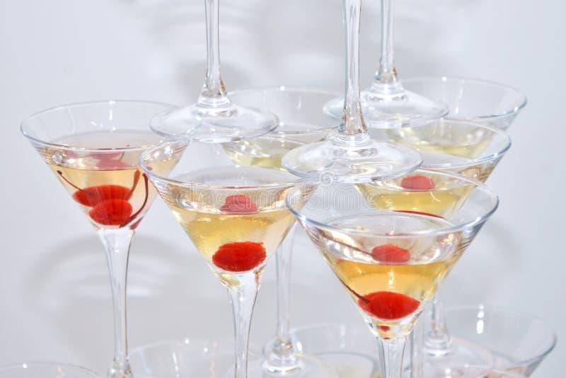 Triangulära martini exponeringsglas som fylls med champagne med körsbär som byggs i formen av en pyramid, bästa sikt royaltyfri foto