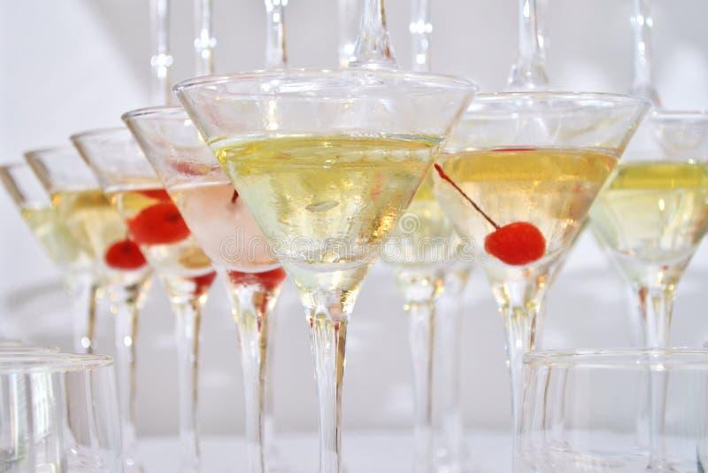 Triangulära martini exponeringsglas som fylls med champagne med körsbär som byggs i formen av en pyramid, closeup royaltyfri fotografi