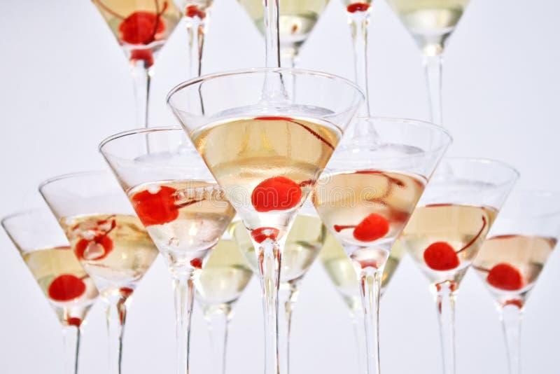 Triangulära martini exponeringsglas som fylls med champagne med körsbär i formen av en pyramid, bottensikt fotografering för bildbyråer