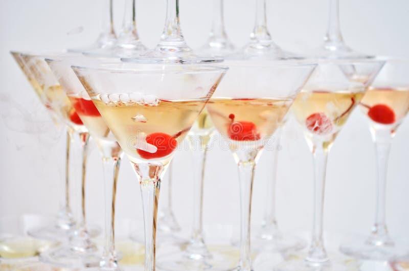 Triangulära martini exponeringsglas som fylls med champagne med körsbär och vätskegasformigt grundämne, i formen av en pyramid royaltyfri bild