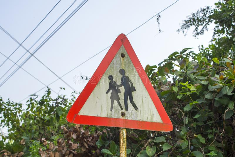 Triangulärt vägmärkevarningsfolk på en bakgrund av gröna buskar arkivfoto
