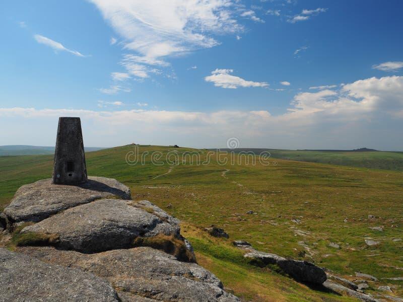 Triangulacyjny filar na tak Tor patrzeje Wysoki Willhays z bielem chmurnieje w niebieskim niebie, Dartmoor zdjęcie stock