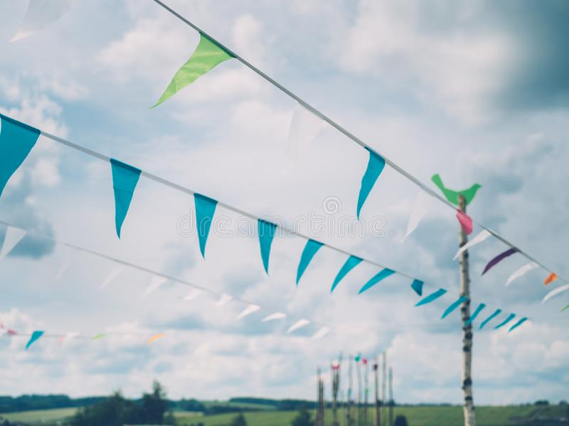 Triangular flags on the rope against clouds during summer festival. Cheerful colourful decoration at country summer festival royalty free stock images