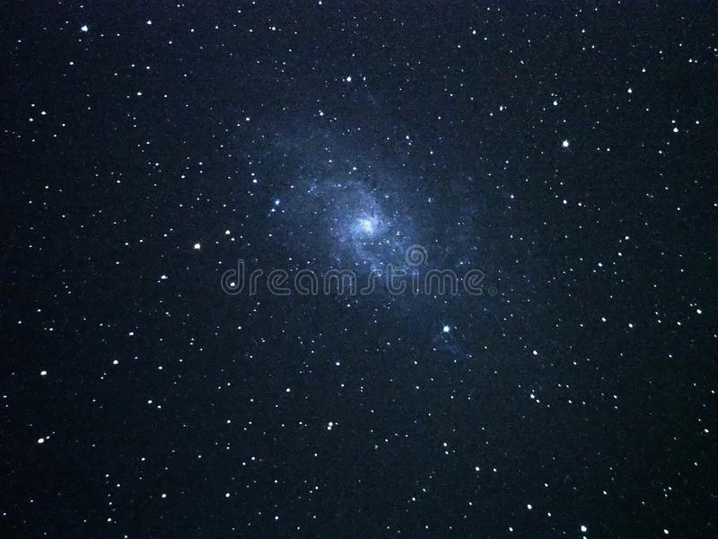 Universe stars and spiral galaxy M33 over telescope royalty free stock image