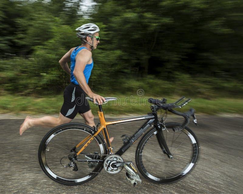 Triathlete con una bicicletta immagine stock libera da diritti