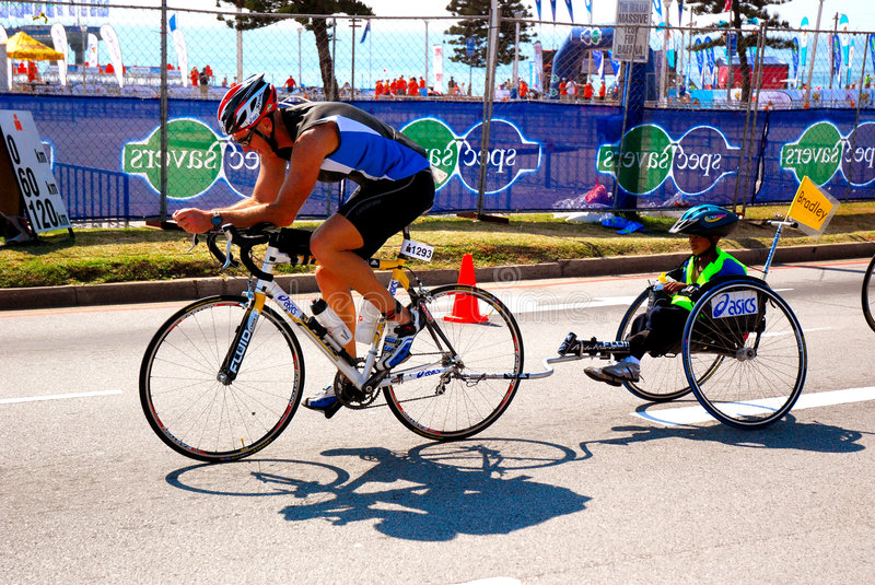 Triathlete with disadvantaged kid. A Caucasian triathlete cycling a disadvantaged black child who is sitting in a trailer of the bike. They are participating in royalty free stock images
