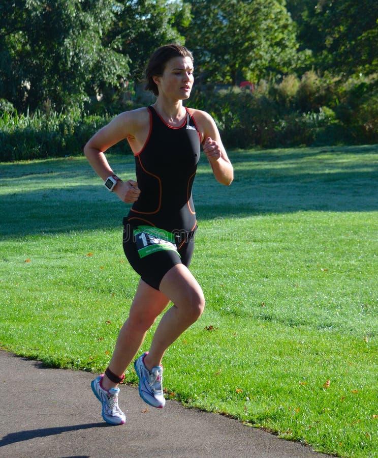 Triathlete fêmea que corre em Skinsuit preto imagem de stock
