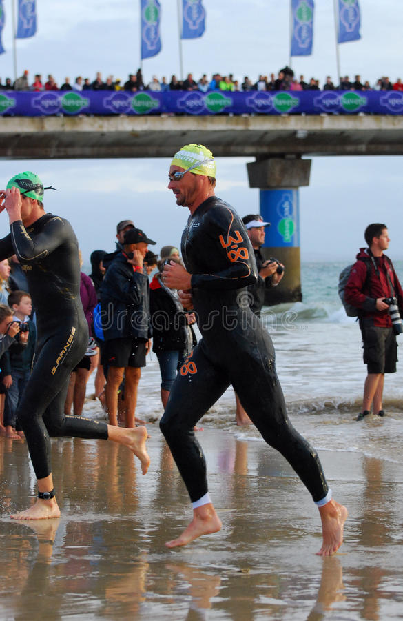 Triathlete running out of water stock photo