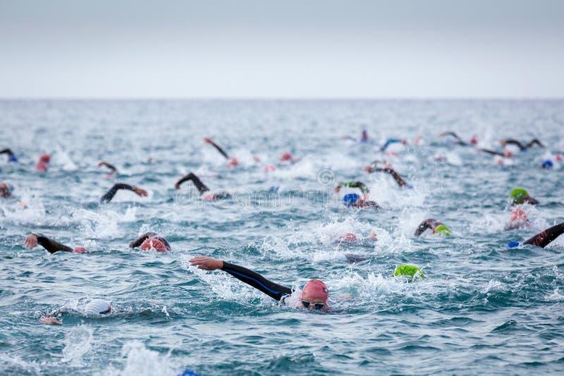 Triathletes in acqua nella concorrenza di triathlon di Ironman alla spiaggia di Calella fotografie stock libere da diritti