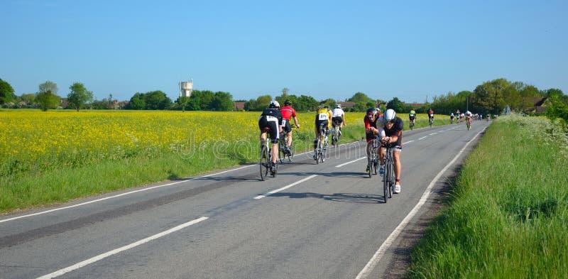 Triathletes auf Radfahrenstadium der Straße des Triathlonreitens in beiden Richtungen stockfoto