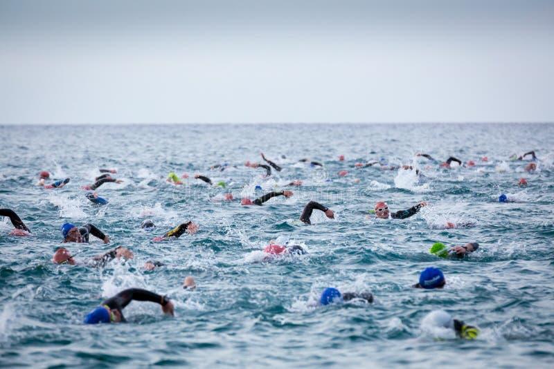 Triathletes im Wasser im Ironman-Triathlonwettbewerb an Calella-Strand stockfotos