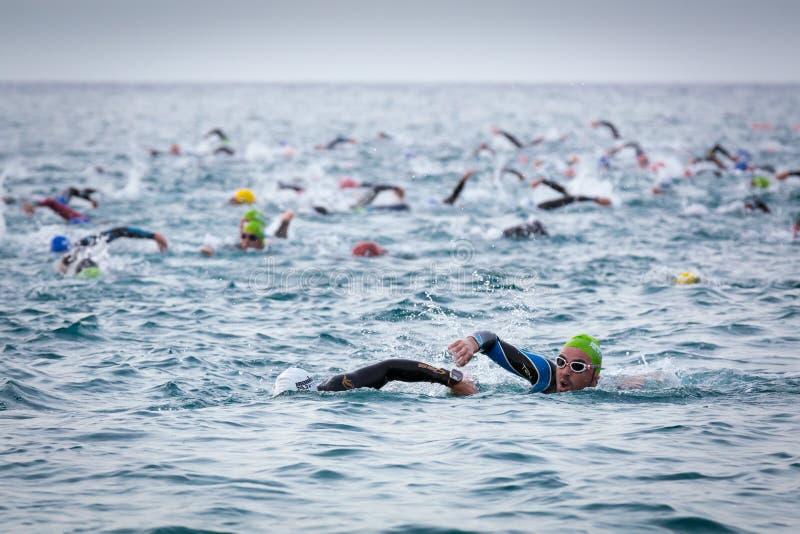 Triathletes swim on start of the Ironman triathlon competition royalty free stock photography