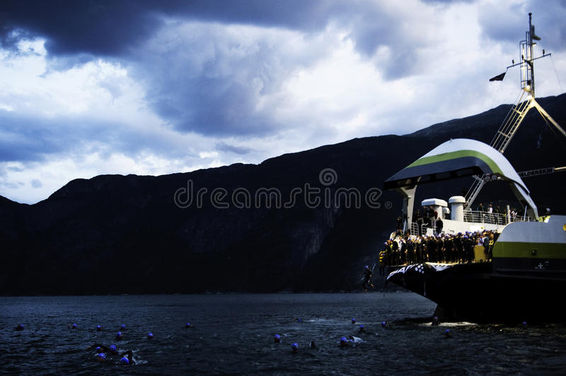 Triathlon. The Athletes jump out of the ferry and into the icecold water in the fjord. The drop is 5m and the race is about to begin. Norseman Extreme Triathlon royalty free stock images