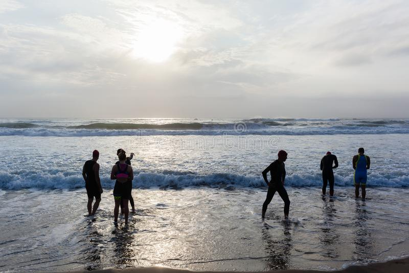 Triathlon Athletes Beach Swim. Triathlon beach athletes silhouetted swim preparation for race start in ocean water course at dawn sunrise royalty free stock photography