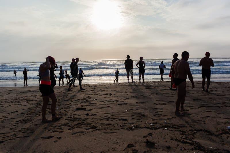 Triathlon Athletes Beach Ocean Swim Start. Triathlon beach athletes silhouetted swim preparation for race start in ocean water course at dawn sunrise royalty free stock image