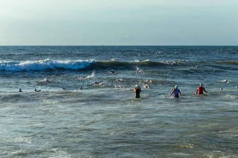 Triathlon Champs Ocean Swim Start. Triathlon National Champs Durban,South-Africa - March 24 , 2019 :Athletes running off beach entering ocean wave surf for royalty free stock images