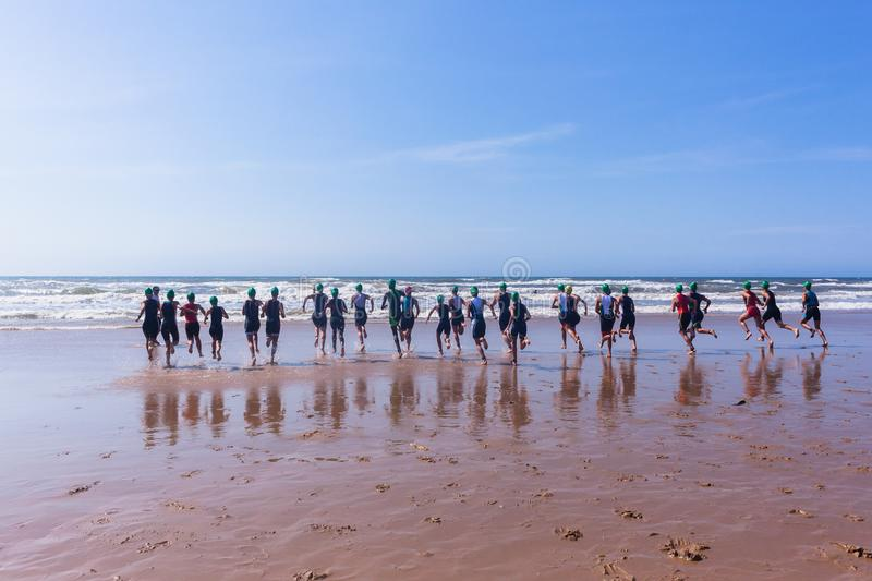 Triathlon Champs Teenagers Ocean Swim Start. Triathlon National Champs Durban, South-Africa - March 24 , 2019 : Athletes teenagers running off beach entering stock images