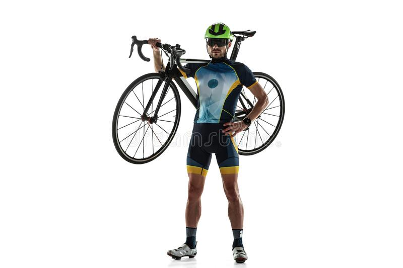 Triathlon male athlete cycle training isolated on white studio background. Caucasian fit triathlete practicing in cycling wearing sports equipment. Concept of stock image