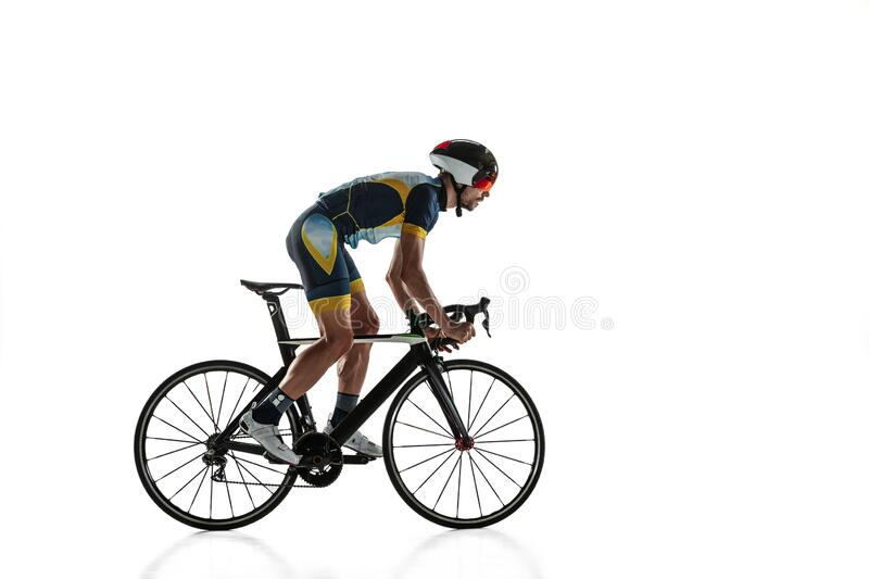 Triathlon male athlete cycle training isolated on white studio background. Caucasian fit triathlete practicing in cycling wearing sports equipment. Concept of royalty free stock image