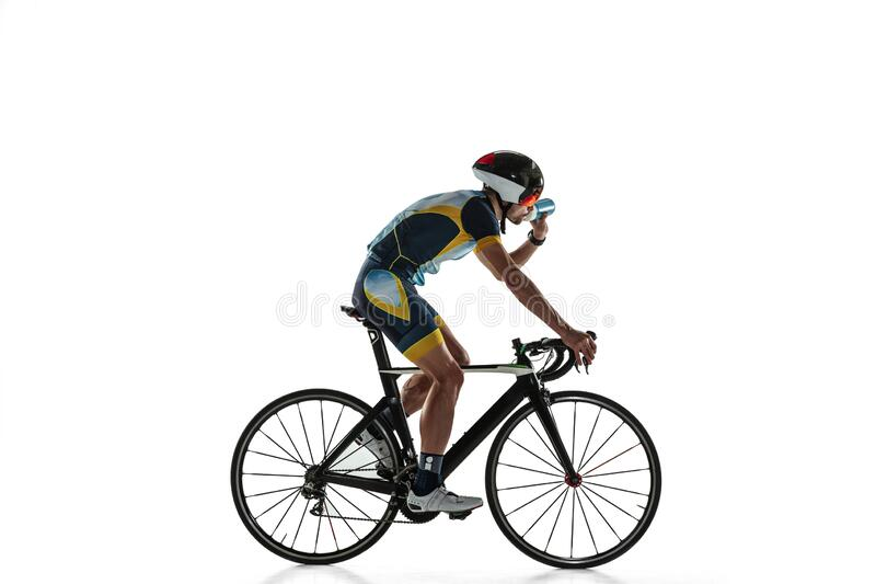 Triathlon male athlete cycle training isolated on white studio background. Caucasian fit triathlete practicing in cycling wearing sports equipment. Concept of stock photos