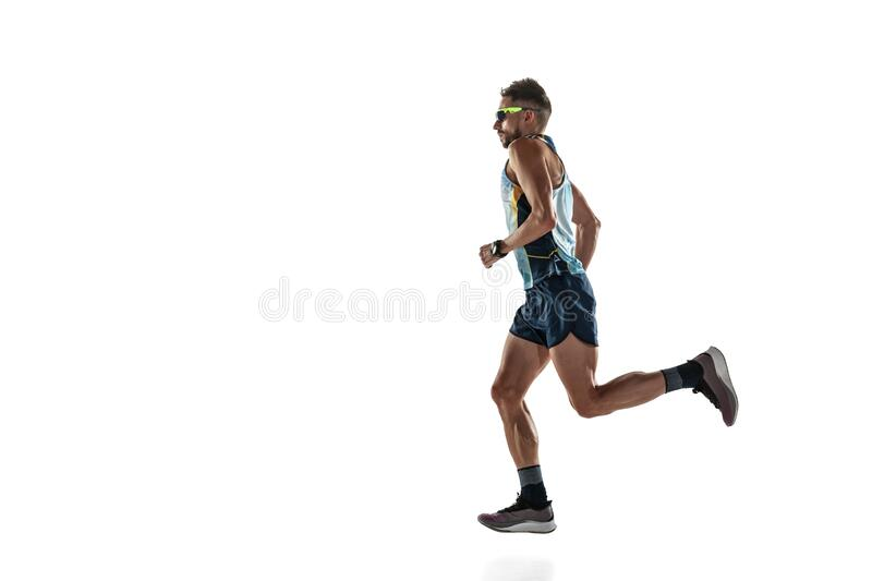 Triathlon male athlete running isolated on white studio background. Caucasian fit jogger, triathlete training wearing sports equipment. Concept of healthy royalty free stock image