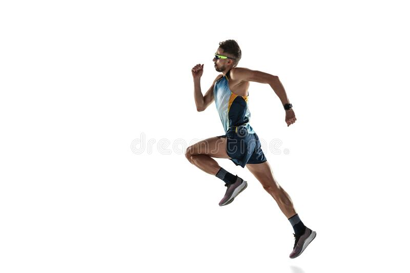 Triathlon male athlete running isolated on white studio background. Caucasian fit jogger, triathlete training wearing sports equipment. Concept of healthy royalty free stock images