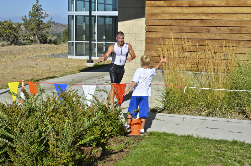 Triathlon Racer. Boy reaches for a high-five as a triathlon racer passes by royalty free stock photo