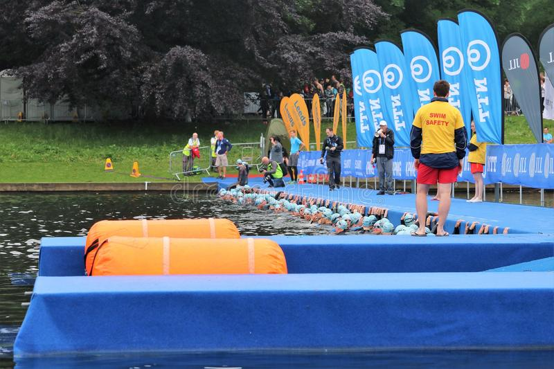 Triathlon triathletes healthy exercise sport swim. Triathletes line up in the water next to a pontoon ready for the start of a triathlon at Roundhay Park, Leeds royalty free stock photography