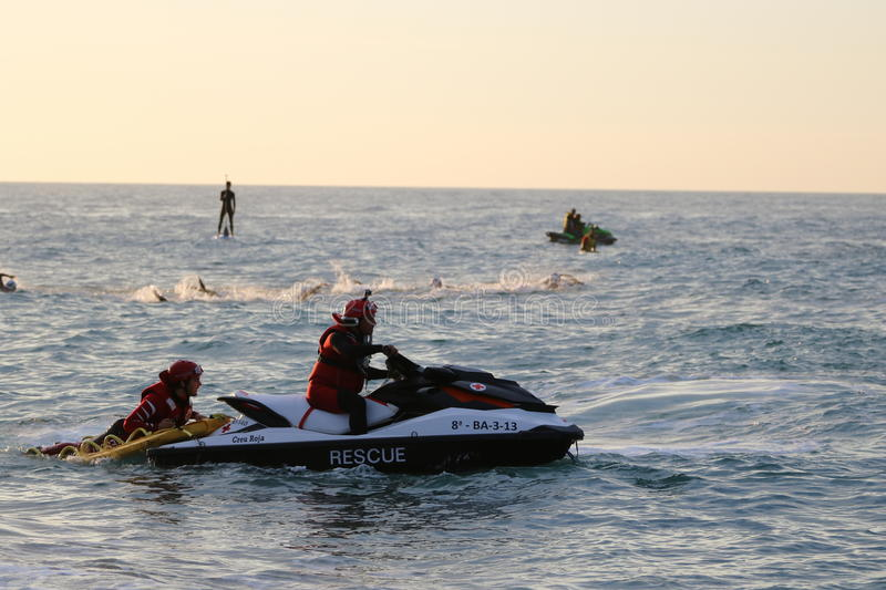 Triathlon triathletes sport healthy exercise safety boat swim. A safety boat watches over triathletes as they swim at the dawn start to Ironman 70.3 Barcelona royalty free stock photography