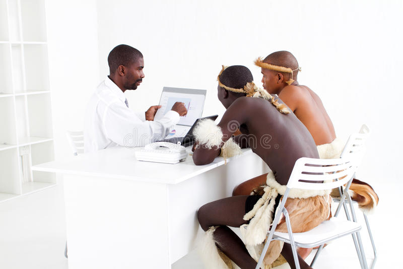 Tribal business. Modern south african business man consulting with two traditional tribal male clients stock photography