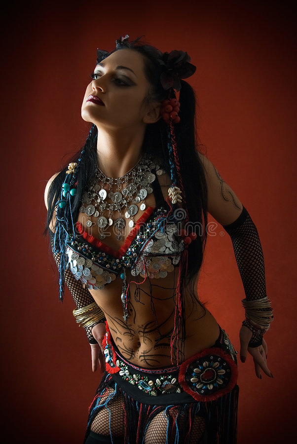 Tribal dancer in dark. Young beautiful tribal dancer woman on red background royalty free stock photography