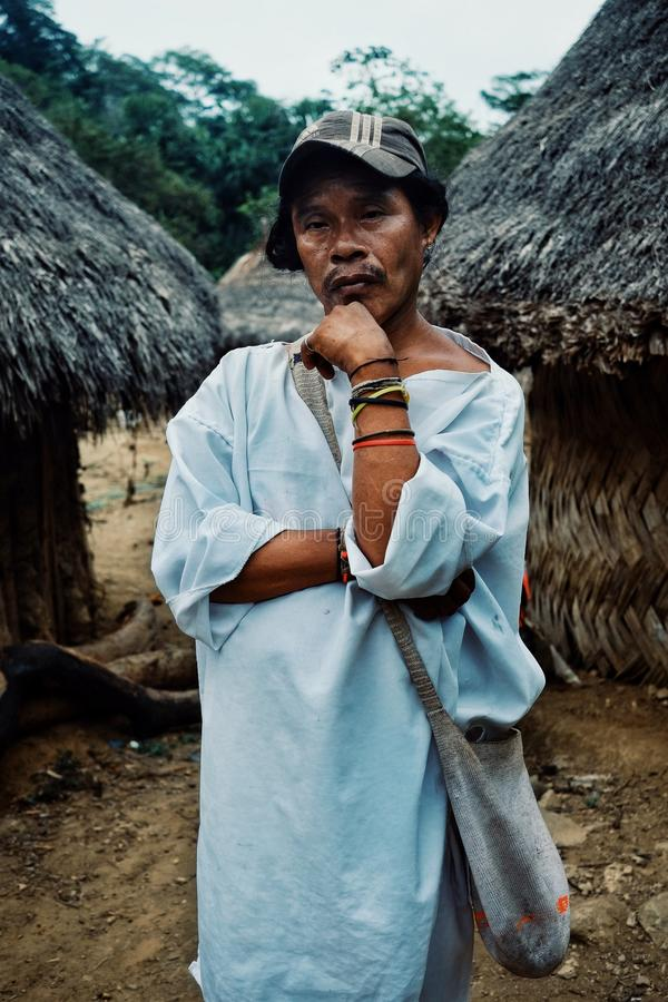 Tribal kogi man in front of ceremonial buildings in the middle of the cloudfor. Santa Marta, Magdalena / Colombia - MARCH 10 2016 : tribal kogi man in front of royalty free stock photo