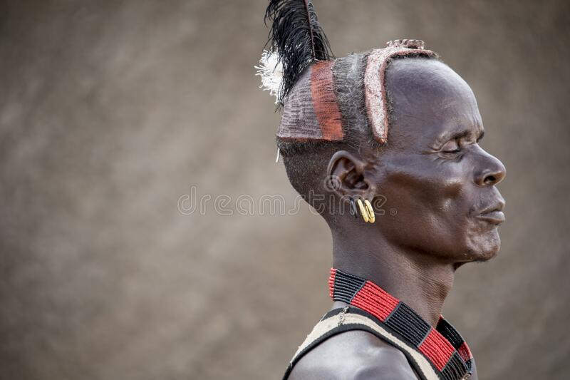 Tribal man with eyes closed wearing traditional head gear royalty free stock photography