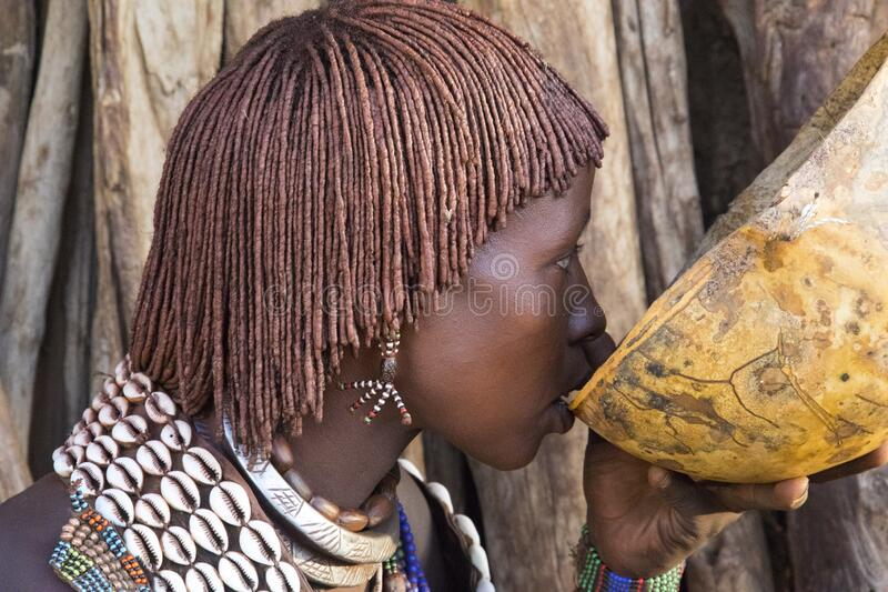 Tribal woman drinking from a eco friendly container stock image